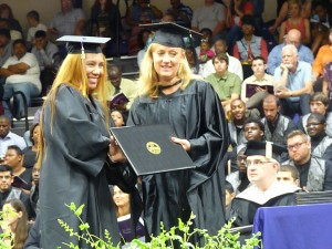 CPS VP Kelly Kelley-Sanders hands a diploma to another CPS Grad